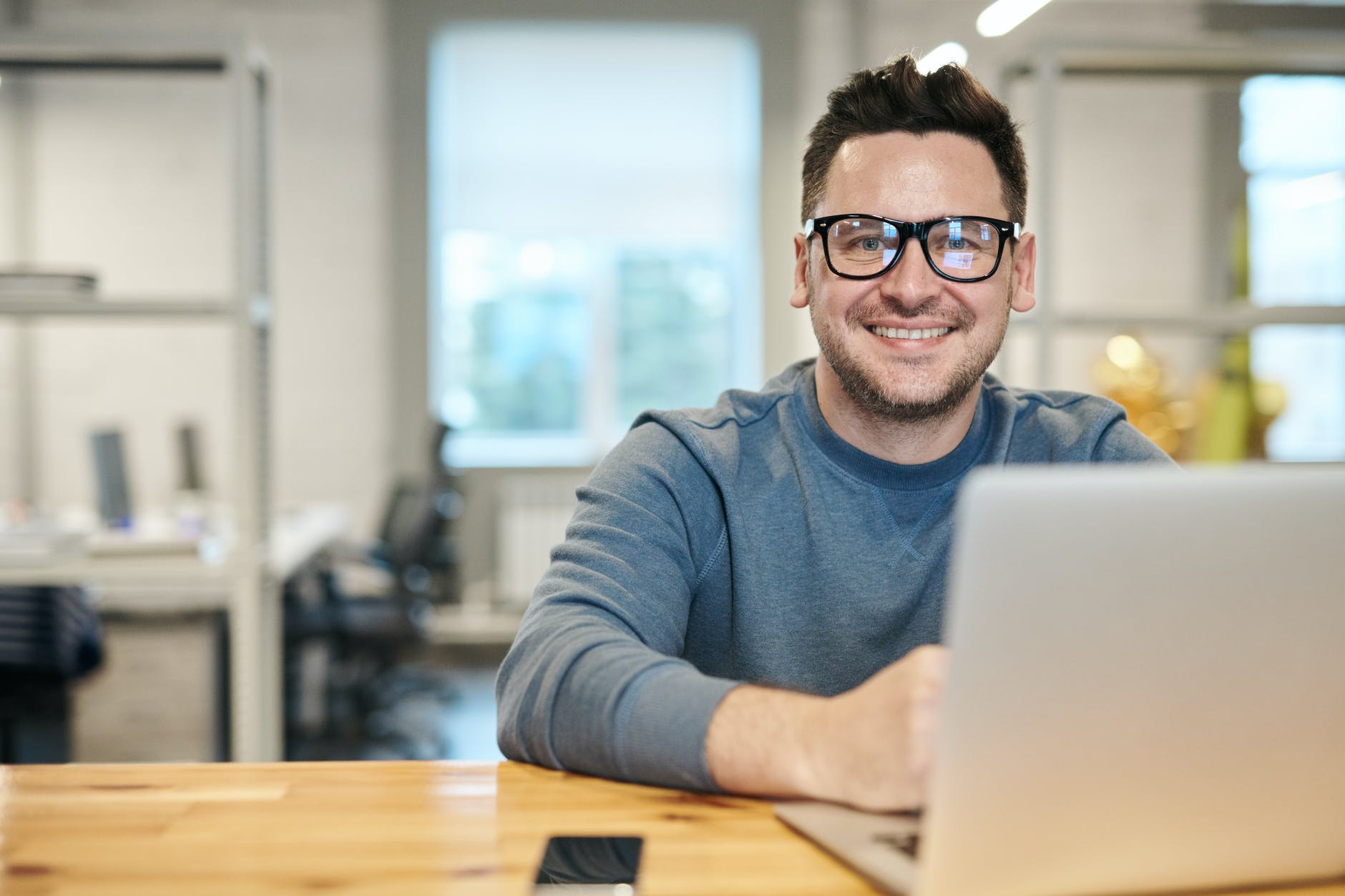 Smiling man with glasses sat down in front of laptop