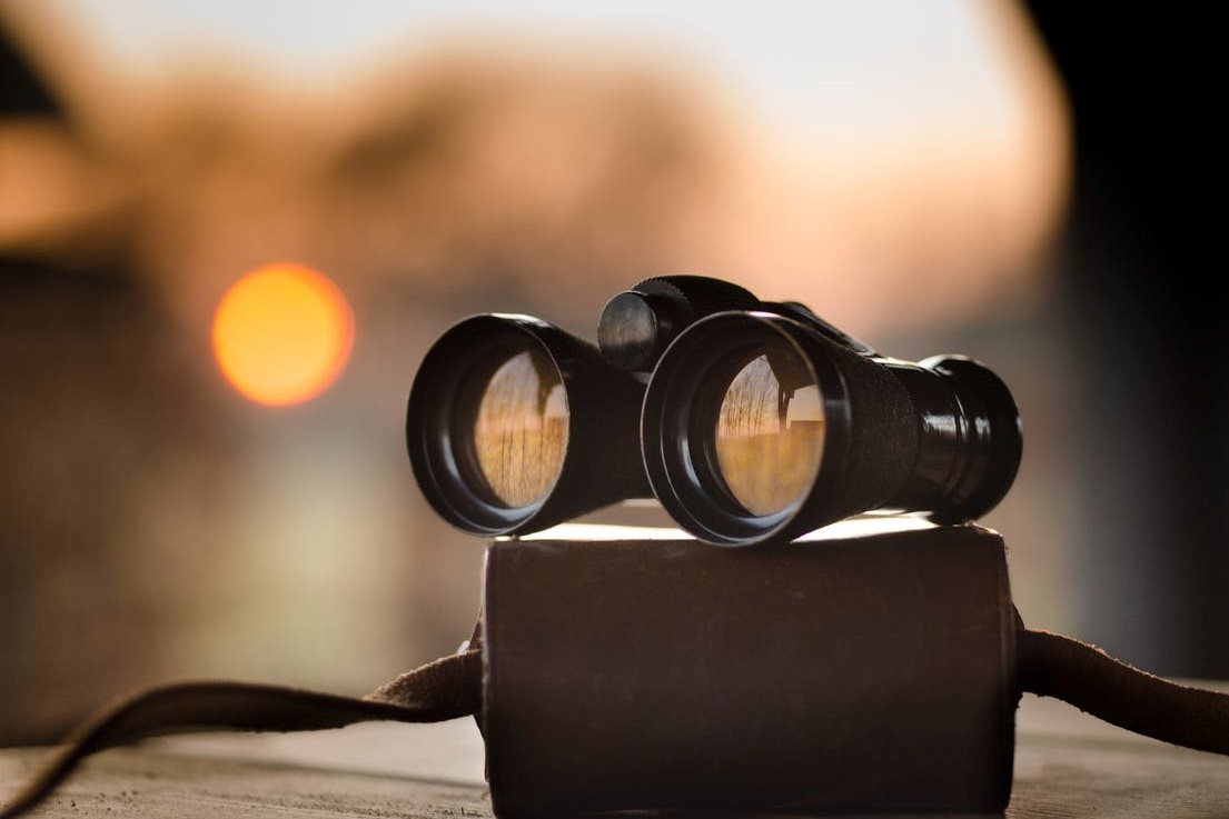 Binoculars on a book at sunset.
