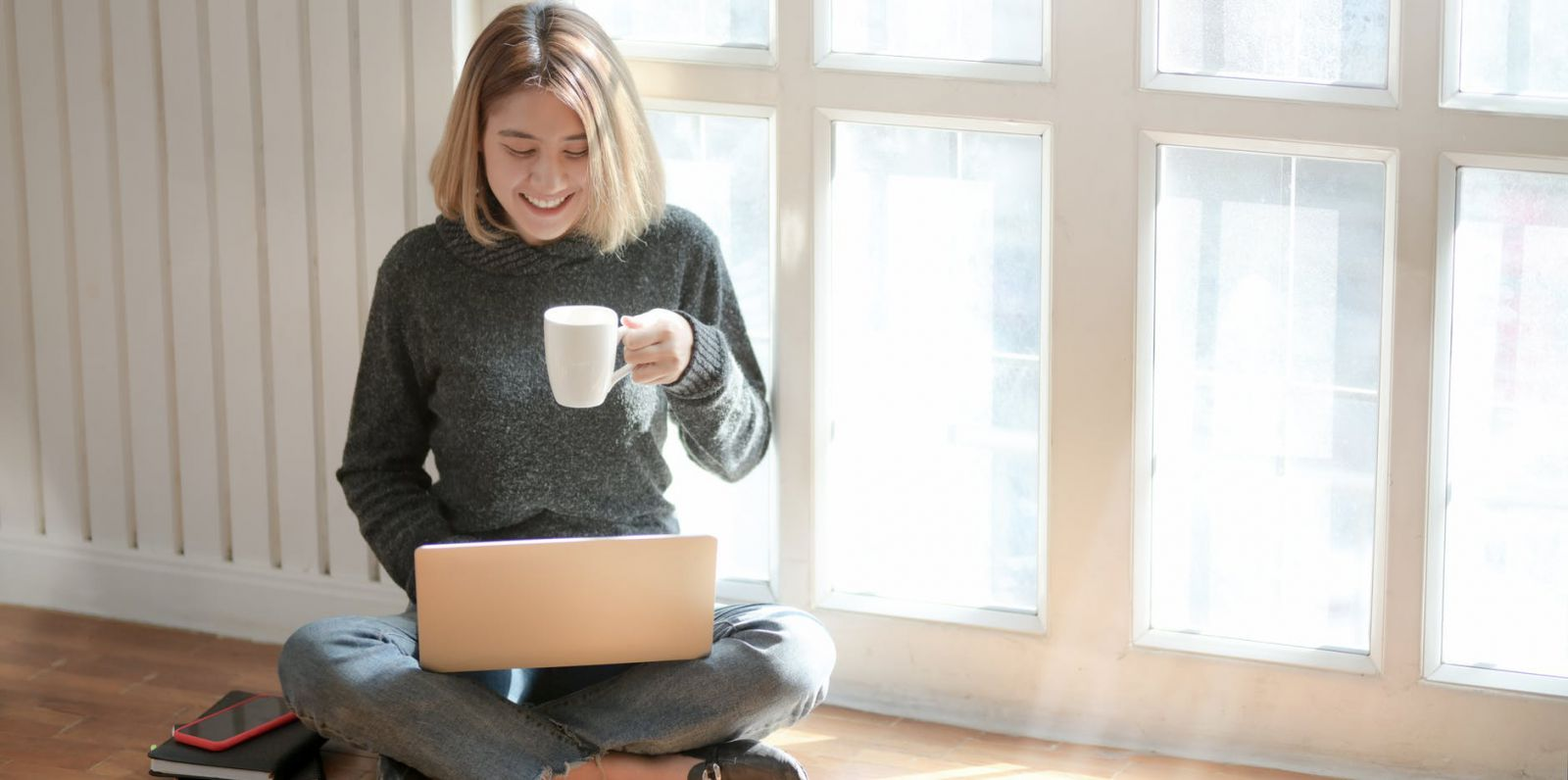 A woman drinking coffee while searching on her laptop