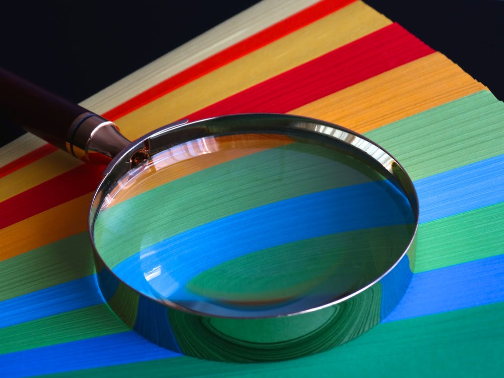 Magnifying glass atop coloured card